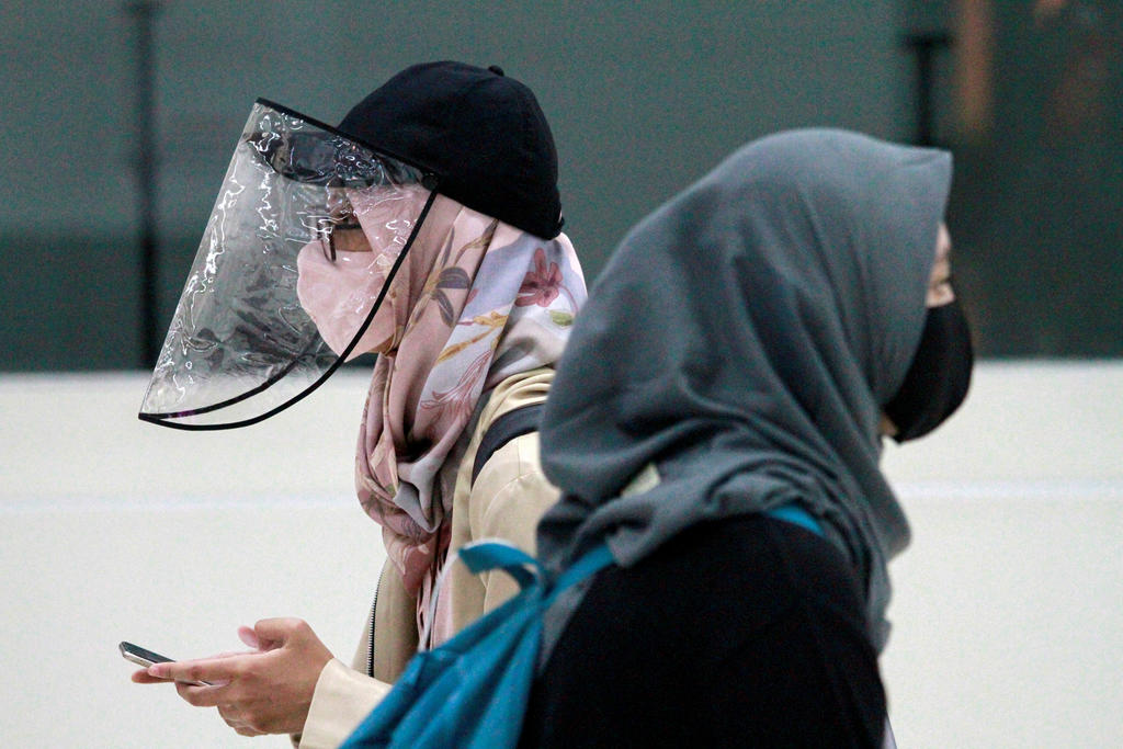 Women are pictured wearing a protective face mask and face shield as the Indonesian government eases restrictions to prevent the spread of the coronavirus disease (COVID-19) outbreak in Jakarta, Indonesia.